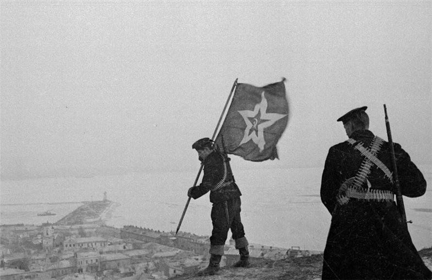 Советские морские пехотинцы устанавливают корабельный гюйс на самой высокой точке Керчи — горе Митридат.  Крым.  Окончательно город был освобожден от захватчиков 11 апреля 1944 года. Еще в октябре — ноябре 1943 года гитлеровцы провели насильственную эвакуацию населения Керчи и ее окрестностей, укрывавшихся расстреливали. В момент освобождения в городе оказалось только 30 жителей. Апрель 1944 г. Автор: Евгений Халдей