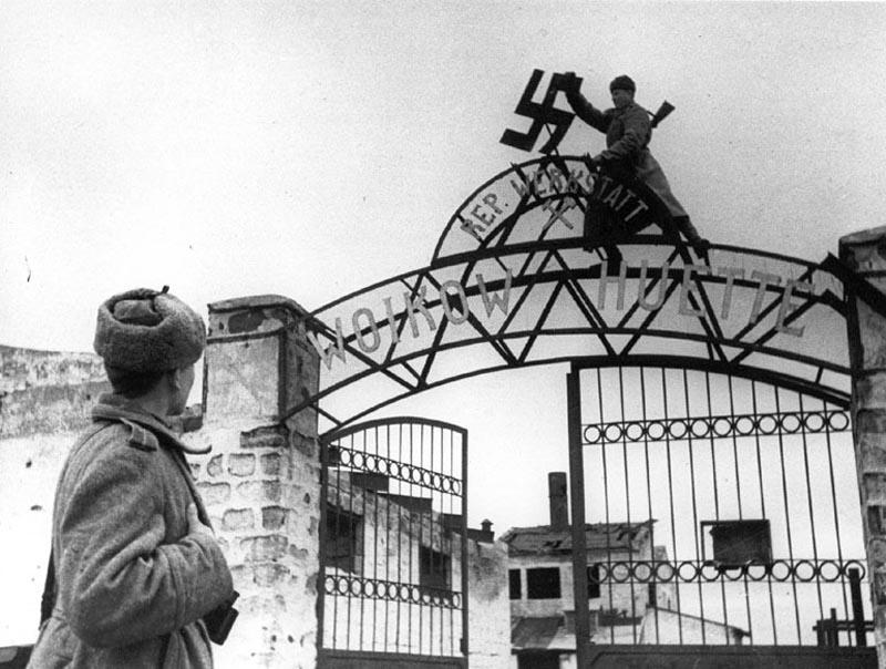 Советский солдат срывает нацистскую свастику с ворот металлургического завода им. Войкова в освобождённой Керчи. Окончательно город был освобождён от захватчиков 11 апреля 1944 года.  Завод им.Войкова был ареной ожесточённых боёв в ходе крушения Крымского фронта и сдачи Керчи в мае 1942 года. Здесь оборонялись сводные отряды 44-й армии , прикрывавшие переправу отступавших советских войск через Керченский пролив. Активная фаза обороны длилась с 18 мая до 05 августа 1942 года, после этого остатки защитников спустились в подземные коммуникациии завода и оттуда продолжили борьбу с оккупантами. Последняя перестрелка на заводе им.Войкова датируется декабрём 1942 года. Апрель 1944 г. Автор: Евгений Халдей.