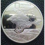 На Украине выпустили монету с отъезжающим на железнодорожных колесах Крымом