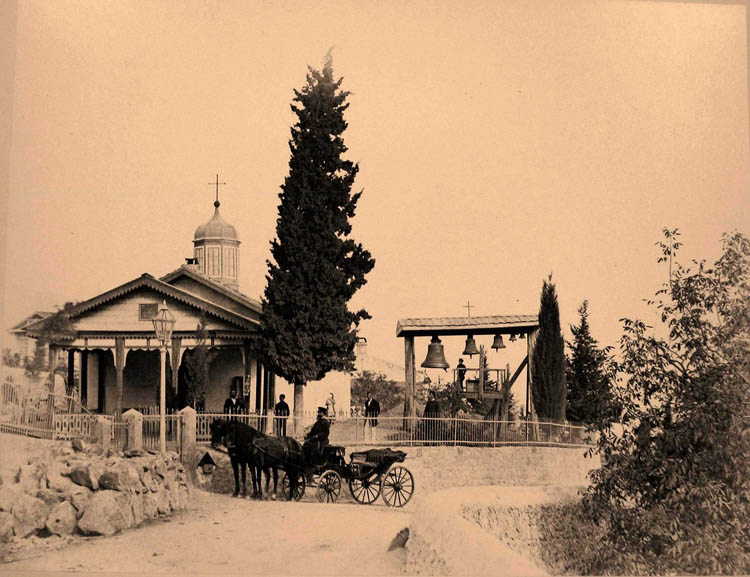 Ялта. Местные жители у входа в церковь Свмч. Феодора Тирона в Верхней Аутке, близ Ялты; справа - звонница